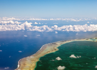 Polynesia. The atoll in ocean through clouds. Aerial view...