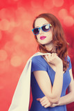 Redhead girl with shopping bags on red background.