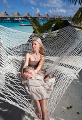 woman in a long sundress in a hammock on a sea background..