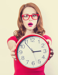 Surprised redhead girl with huge alarm clock on light background