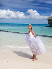 young beautiful woman in a bride dress standing at sea edge..