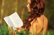 Young naked woman reading book