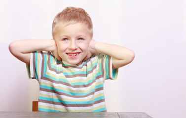 Portrait of blond boy child kid covering ears at the table