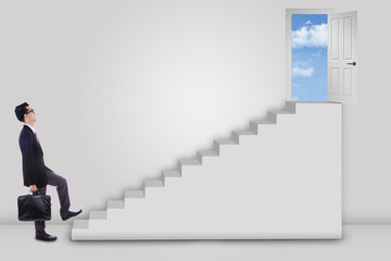 Businessman stepping up ladder to success door