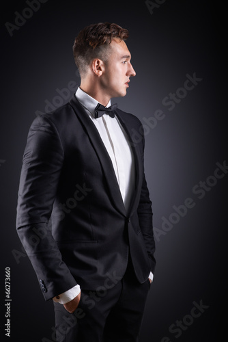 business man in suit on a dark background - 66273660