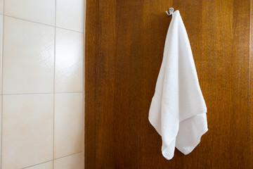 towel hanging on the hook against brown wood background