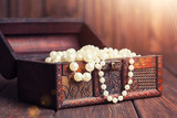 old treasure chest with pearl necklaces standing on wooden table