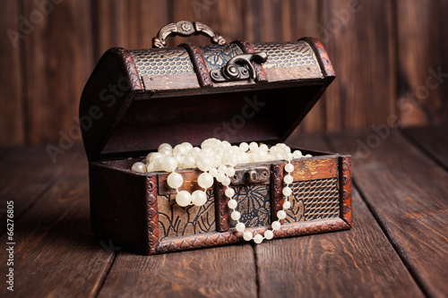 old treasure chest with pearl necklaces standing on wooden table - 66276805