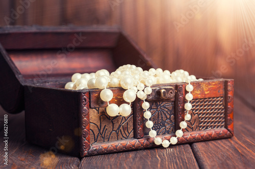 Leinwandbild Motiv old treasure chest with pearl necklaces standing on wooden table