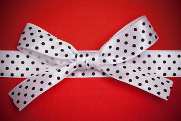 white polka dot ribbon and bow on red background