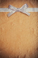 white polka dot ribbon and bow on old paper