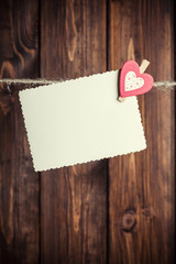 old paper sheet and small paper heart hanging on clothesline aga