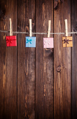 four small gift boxes hanging on clothesline against wooden back