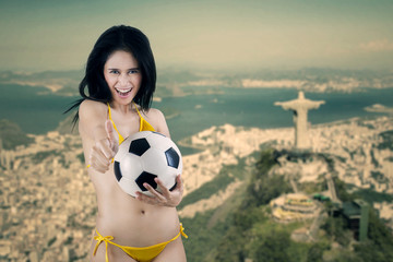 Cheerful woman holding ball in Brazil