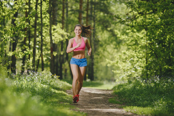 fitness girl running on forest trail and smiling