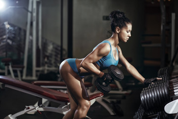 Brunette fitness girl lifting dumbbell