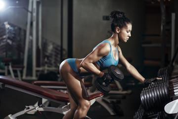Brunette fitness girl lifting dumbbell
