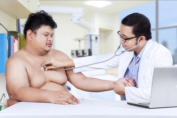 Doctor is checking a fat man