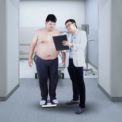 Doctor showing report to a fat patient