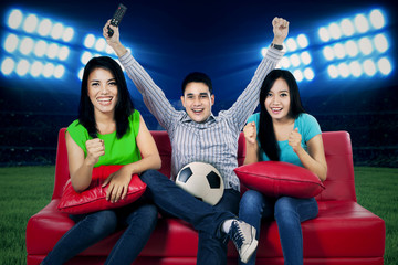 Ecstatic soccer fans watching tv