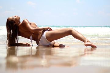 Woman with white bikini posing sexy at the beach