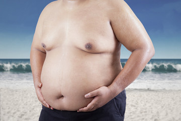 Fat man holding his stomach at beach 1