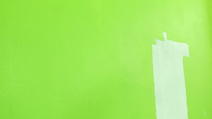 Painter rolls green paint onto a white wall