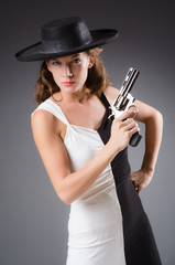Woman with gun against dark background