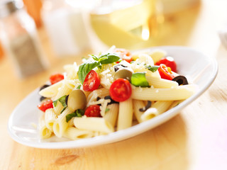 penne pasta salad with olives, tomatoes, and basil.