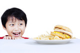 Greed boy looking at fast food poster