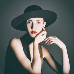 Portrait of young woman in a black hat.