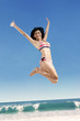 Joyful woman in bikini jumping on beach