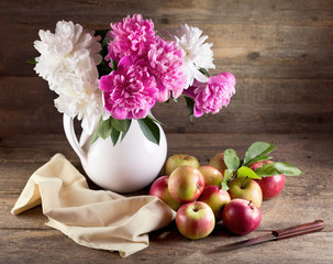 bouquet of peonies and red apples