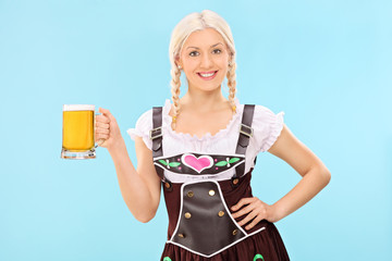 Girl in bavarian costume holding a pint of beer