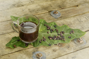 Nontoxic black coffee on elephant ear leaf with wooden table