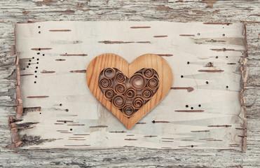 Wooden decorative heart on the birch bark