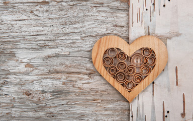 Wooden decorative heart on the birch bark