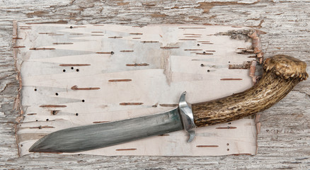 Old knife on the birch bark and weathered wood