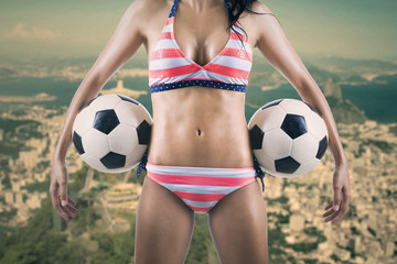 Sexy soccer fan holding two balls