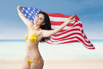 Sexy woman holding american flag at beach