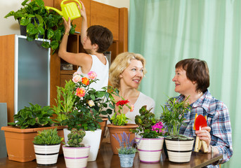 Senior  pensioners  and girl  caring for home  plants