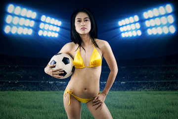 Sexy woman holding soccer ball at field