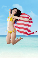 Sexy woman jumping with holding american flag