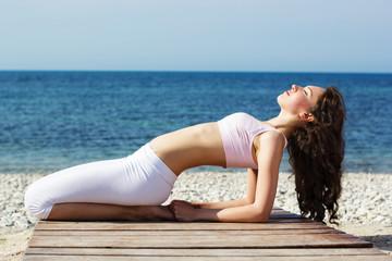 Girl doing yoga exercises on the sea coast