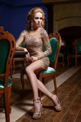 Girl in a shiny dress, sitting on a green chair luxurious hall.
