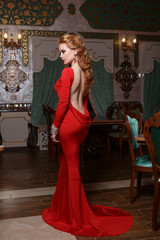 Fashion portrait of young magnificent sexy woman in red dress
