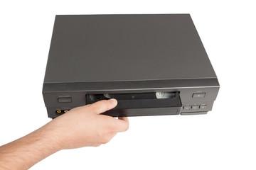 hand inserts videocassette in videorecorder