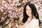 Beautiful young woman in blossom garden