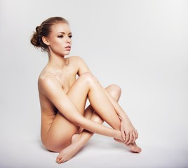 Nude woman sitting on floor