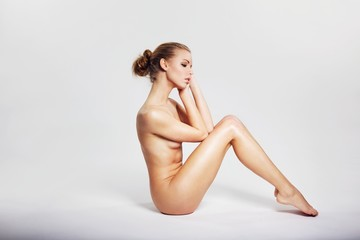 Young nude woman sitting in a nice posture